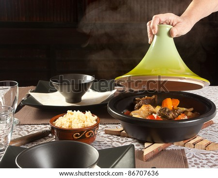 Hand lifting the lid of a steaming moroccan tajine dish