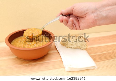 Hand lifts spoonful of vegetable soup from bowl with bread roll and napkin on table