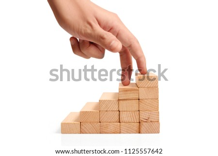 Hand liken business person stepping up a toy staircase #1125557642