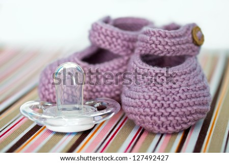 Hand-made baby shoes and a pacifier