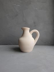 Hand-made ceramic jug (jar) on the grey concrete background