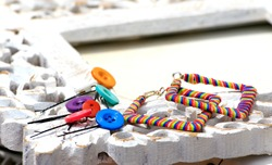 Hand-made earring, hair clips made by button and woolenon on a vintage wooden frame. Handmade or DIY is movement nowadays