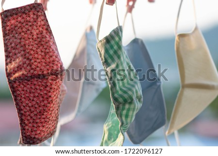 Hand-made face masks made of fabric hang over the window of the room. Washable and reusable, can be used during the shortage of surgical masks due to the corona virus Covid-19. copy space. Foto stock ©