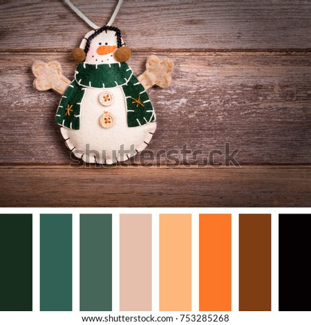 Hand made felt snowman Christmas decoration. Vintage style, over old wood background. In a colour palette with complimentary colour swatches.