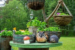 Hand made hanging flower pots and wooden petunia pots in the summer garden. Decorative figures of an owl, hedgehog and mushroom on the table. eco design
