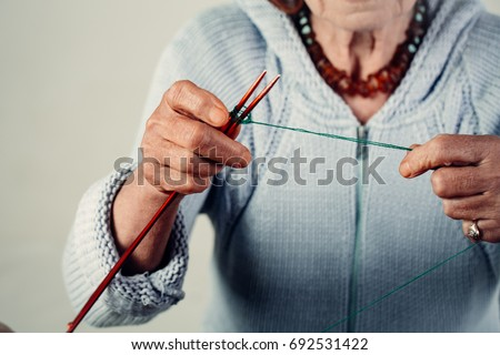 Hand made knitting. Unrecognizable lady wears a knitted sweater for the winter. Warm clothes. Manufacture of wearing apparel. Hobbies and pensions. Female hands knit wool #692531422