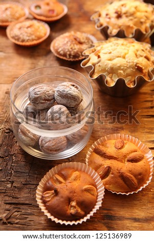 hand-made muffins and jars of colored white walnut on the background of wooden boards