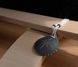 hand made necklace lies on the crosshairs of a wooden structure. the base is made of light wood in the form of a hill, with a rectangular beam on top. geometry. glitters and shimmers in the light