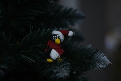hand made penguin in a santa claus  hat with pompon and red scarf sits on branch of the christmas tree and very stares intently