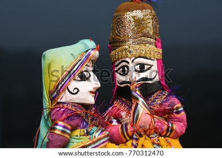 Hand made puppets attached to string, King and queen kissing Rajasthan India. Dolls men, women face wearing traditional dress Saree, Sari, Kurt at Dilli Haat for Dussehra, Dasara, Diwali festival