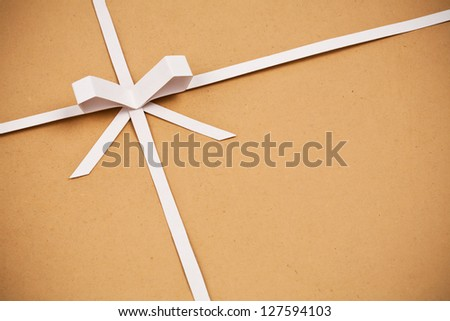 Hand made ribbon and bow on kraft paper as background. Greeting card