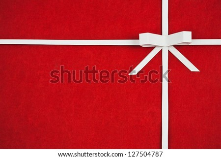 Hand made ribbon and bow on red kraft paper as background. Greeting card