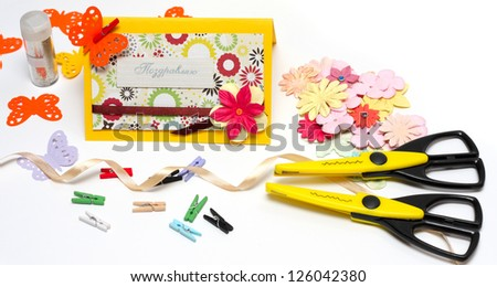 hand made scrapbooking post card and tools lying on a white background