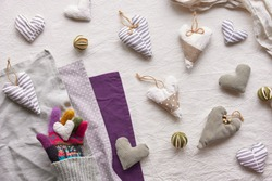Hand made textile hearts and balls on cotton background. Hand holds soft heart. Textile stuffed toys, balls and candle in neutral colors and purple linen. Flat lay, top view. Grey winter window light.
