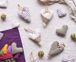 Hand made textile hearts and balls on cotton background. Hand holds soft heart. Textile stuffed toys, balls and candle in neutral colors and purple color. Flat lay, top view. Grey winter window light.