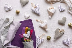 Hand made textile hearts and balls on cotton background. Textile stuffed toys, balls and candle in neutral colors and purple color. Flat grey winter window light.