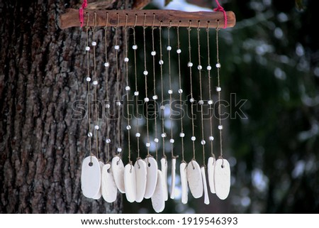 Hand made wind chimes hanging on a string with depth of field effect. Ceramic wind chime hanging outside, selective focus, Wind bells from clay Stock photo ©