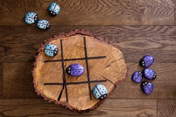 Hand made wood burn tic tac toe game with painted rock game pieces; blue and purple beetles and a wooden x and o game