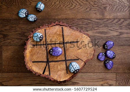 Hand made wood burn tic tac toe game with painted rock game pieces; blue and purple beetles and a wooden x and o game Foto stock ©