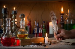 hand, magic potion, ancient books and candles
