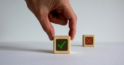 Hand making a choice between two cubes with Yes and No signs on beautiful white background. Business concept.