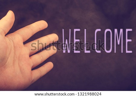 Hand making a welcome gesture on a dark background #1321988024