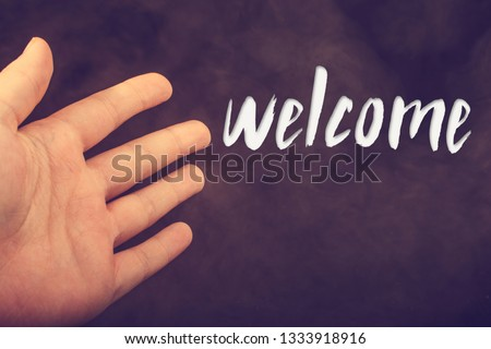 Hand making a welcome gesture on a dark background #1333918916