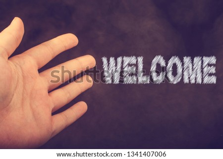 Hand making a welcome gesture on a dark background #1341407006