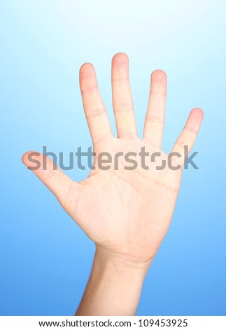 Hand making sign on blue background