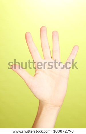 Hand making sign on green background - stock photo