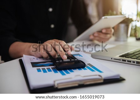 Hand male doing finances and calculate on desk about cost at home office.