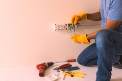 hand man glove hold outlet and connectors conduit on wall, electrician maintenance installation, contractors, craftsman, handyman, plug,  wiring,