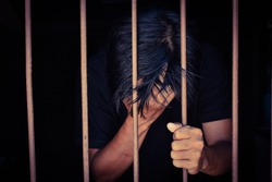 hand man hold steel in jail and holding head on black background.concept for prisoner,sadness,detain,erroneousness