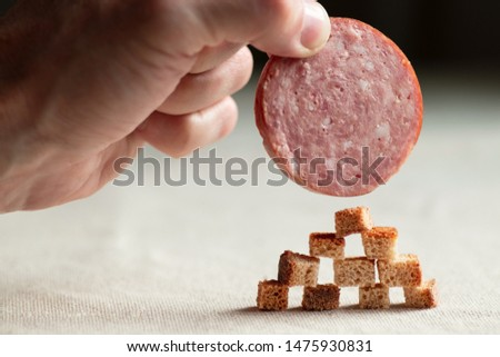 Hand man sets the final element in the form of a slice of sausage on an improvised structure of breadcrumbs. An abstract symbol of building and climbing to the top by the force of one's own efforts.