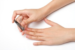 hand manicure with nail clipper on white background