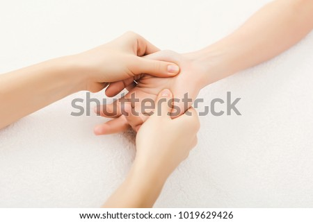 Hand massage. Physiotherapist pressing specific spots on female palm. Professional health and wellness acupressure manipulations, copy space, closeup