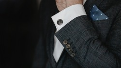 Hand men wears cufflinks close up.