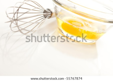 Hand Mixer with Eggs in a Glass Bowl on a Reflective White Background.