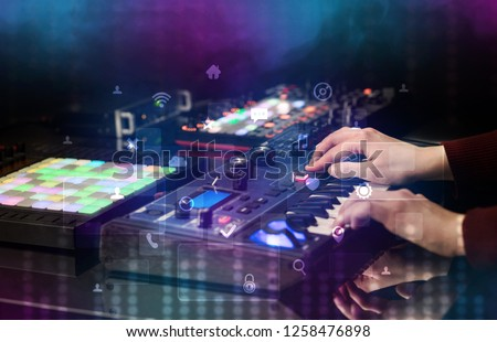 Hand mixing music on dj controller with social media concept icons #1258476898