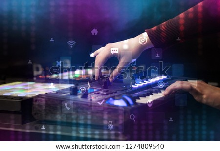 Hand mixing music on dj controller with social media concept icons #1274809540