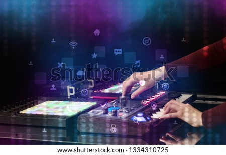 Hand mixing music on dj controller with social media concept icons #1334310725