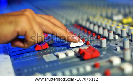 Hand moving the level on proffesional audio mixer. Focus have a little DOF , near hand.