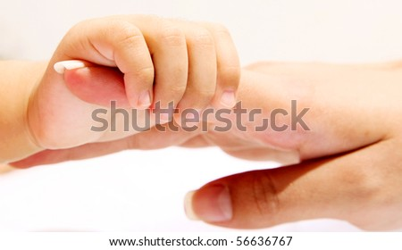 Hand of a baby taking his mother\'s hand. Concepts: Love, family and unit
