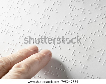 Hand of a blind person reading some braille text touching the relief. Empty copy space for Editor Horizontal
