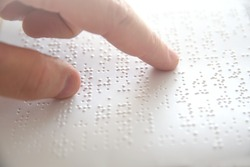 Hand of a blind person reading some braille text touching the relief. Empty copy space for Editor's content.