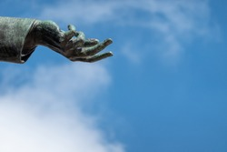 Hand of a bronze statue, open to show the will to peace