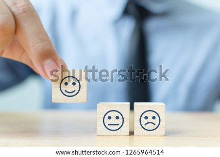 Hand of a businessman chooses a smiley face on wood block cube, The best excellent business services rating customer experience, Satisfaction survey concept #1265964514
