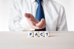Hand of a businessman presenting the wooden cubes with the word fact. Facts, truth or accurate information in media news or business concept.