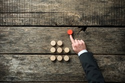 Hand of a businessman pushing red wooden cut circle out of the crow of others in a conceptual image of self initiative and determination.