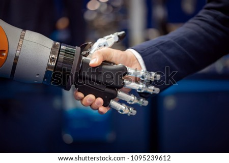 Hand of a businessman shaking hands with a droid robot. The concept of human interaction with artificial intelligence.